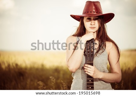 cool young woman in red hat with guitar at spring meadow - stock photo