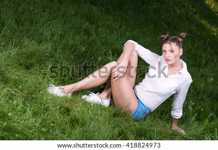 Cool young woman posing sitting on the grass. A modern, casual look. Short shorts and a white shirt. Hairstyle and light makeup