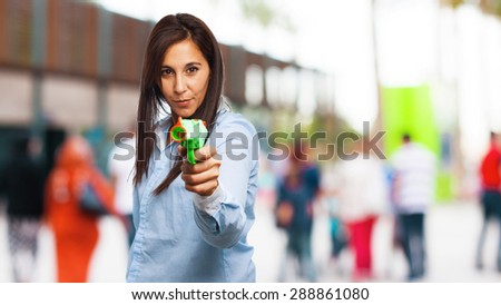cool young woman with pop gun - stock photo