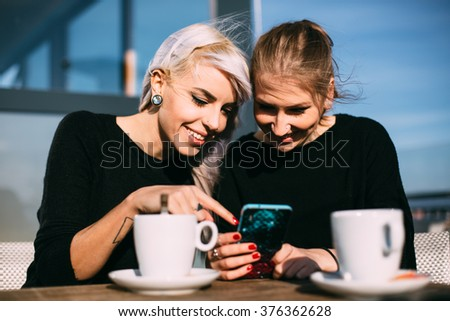 Cool young women using smartphone in coffee shop - stock photo