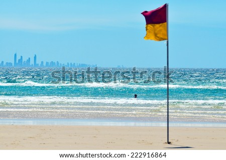 COOLANGATTA - OCT 07 2014:Australian person swim at sea beside a Lifeguards flag.According to Australia National Drowning report 300 people drown in 2012 with cost of $1 billion to Australian economy.