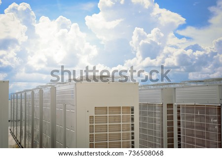 Cooling air conditioner condenser fan units on top building roof and blue sky background.Air conditioning system for building.
