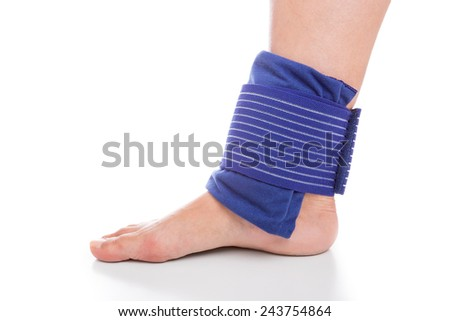 Cooling and bandage the foot. Sports injuries. - stock photo
