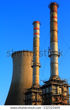 Cooling tower and metal chimneys of an electrical plant - stock photo