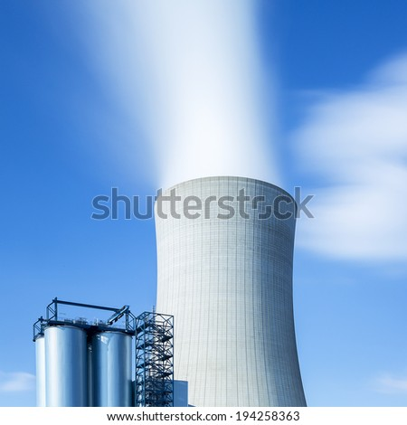 cooling tower from a  power plant with steam on blue cloudy sky