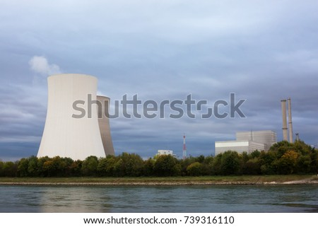 Cooling towers of a nuclear power plant on the Rhine river. Nuclear power concept image, works both for or against nuclear energy.