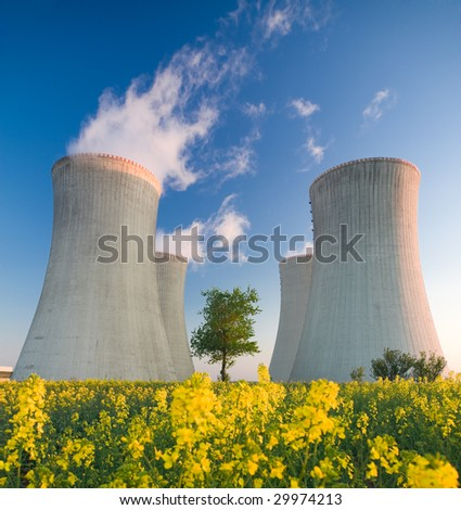 Cooling towers of a nuclear power plant with steam escaping toward the sky.  Flowering landscape in the foreground, and a single tree growing between the two sets of towers. - stock photo