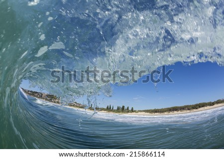 Coolum Beach/ The view of Coolum Beach and town from the sea as a wave pitches over. The way a surfer sees when surfing. Coolum is a surf beach on the Sunshine Coast of Queensland, Australia.  - stock photo