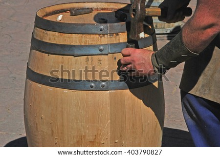 Cooper hands fixing wine wood with chisel and hammer. Making a wooden barrel. Cooperage