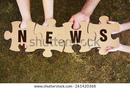 Cooperation - Jigsaw Puzzles in Teams Hands spelling out news - stock photo