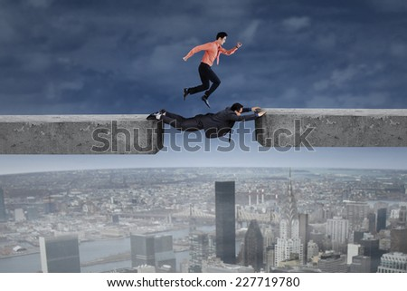 Cooperation of two businessmen through the gap as their obstacle - stock photo