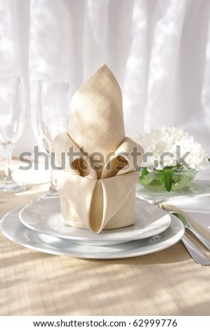 Coordinated decorative napkin on a plate with cutlery - stock photo