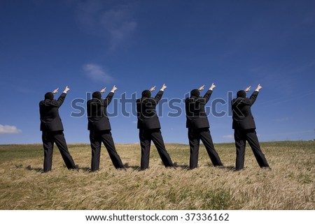 coordinated group of businessman pointing to the same side - stock photo