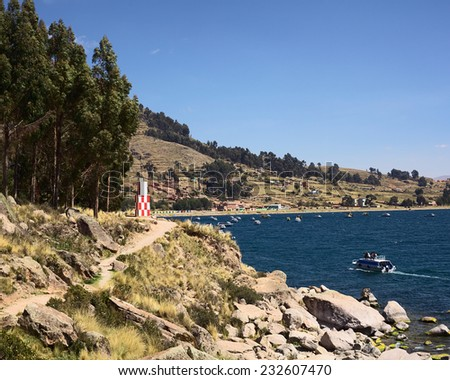 COPACABANA, BOLIVIA - OCTOBER 17, 2014: Beacon on shore of Lake Titicaca at the small tourist town on October 17, 2014 in Copacabana, Bolivia. In back, a tour boat is entering the bay of Copacabana.