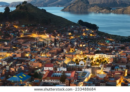 COPACABANA, BOLIVIA - OCTOBER 24, 2014: View shortly after sunset over the small touristy town and Lake Titicaca on October 24, 2014 in Copacabana, Bolivia. In the lower part the basilica is visible. - stock photo