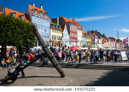 COPENHAGEN - AUGUST 11: Tourists at Nyhavn on August 11, 2012. Nyhavn (literally meaning new harbour) is a 17th-century waterfront, canal and entertainment district in Copenhagen, Denmark.