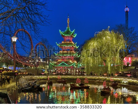 COPENHAGEN, DENMARK - DECEMBER 14, 2015: Evening view of Tivoli Gardens with Chinese pagoda, Dragon Boat lake and Daemonen roller coaster. Tivoli Gardens is the most-visited theme park in Scandinavia. - stock photo