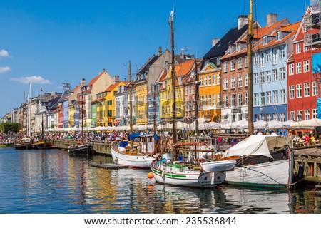 COPENHAGEN, DENMARK - JULY 25: Nyhavn district is one of the most famous landmark in Copenhagen. People enjoy sunny weather in open cafees in Copenhagen on July 25, 2014 - stock photo