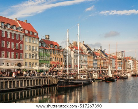 COPENHAGEN, DENMARK - 2014 Jun 10: Perspective view of Nyhavn promenade (pier) with color buildings, ships, yachts and boats in the Old Town -  most famous landmark in the city