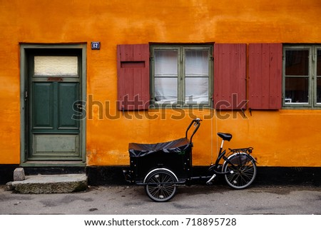 Copenhagen, Denmark - March 01, 2014: Ttraditional danish tricycle standing in front of an orange house.