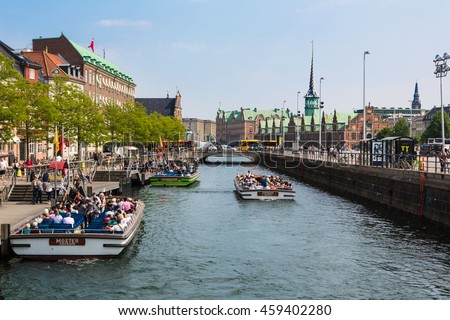 COPENHAGEN, DENMARK - MAY 24, 2016: Tourists enjoy the traditional architecture from a tourist boat along the canals of Denmark capital city on a sunny summer day.