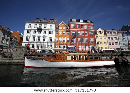 COPENHAGEN, DENMARK - SATURDAY, AUGUST 22, 2015: Boats people crowd the docks surrounding Nyhavn. Nyhavn is a 17th-century waterfront, canal and entertainment district in Copenhagen - stock photo