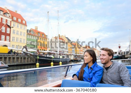Copenhagen tourists people on cruise boat tour on water canal in old port Nyhavn. Young multiracial couple visiting famous European destination in Europe during fall or spring. - stock photo