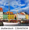 COPENHAGEN: Yacht and Nyhavn in the center of Copenhagen, Denmark. Nyhavn is old waterfront and canal district in Copenhagen. It is lined by colored houses, bars and restaurants. - stock photo