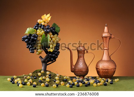 Copper carafe and fresh grapes on the table - stock photo