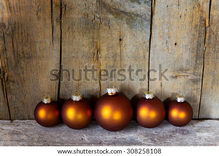 copper colored christmas balls in front of a wooden wall - stock photo