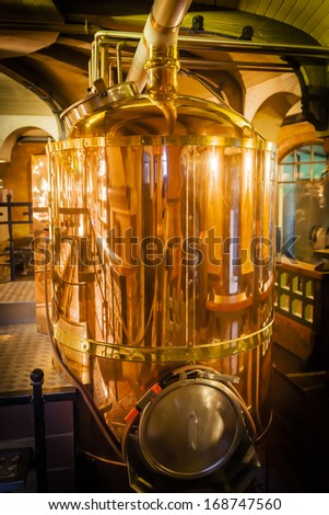 Copper container for brewing, many reflections of light.  - stock photo