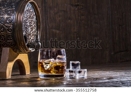 Copper forged barrel and a glass of whiskey and ice on a old table - stock photo