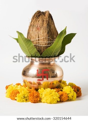 copper kalash with coconut and mango leaf with floral decoration. essential in hindu puja, front view, closeup - stock photo
