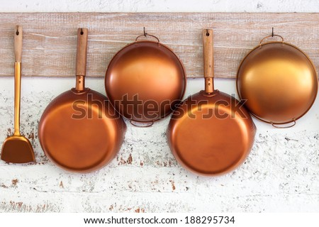 Copper  kitchen utensil on the white painted brick wall - stock photo