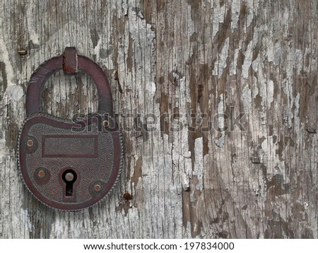 copper padlock on a weathered old wooden floor, with space for text or symbol - stock photo