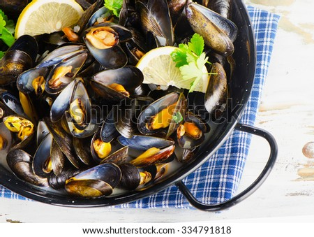 Copper pot of gourmet mussels  garnished with lemon slices. Top view - stock photo