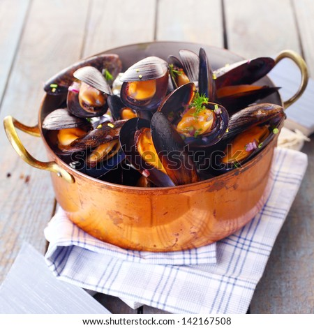 Copper pot of gourmet mussels served on a napkin garnished with fresh herbs for a tasty seafood meal