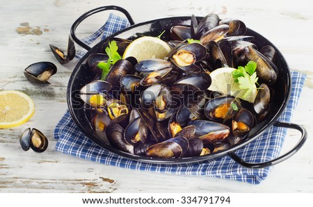 Copper pot of mussels garnished with lemon slices. Selective focus - stock photo