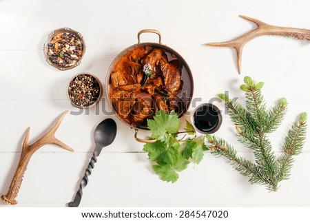 Copper, pot of spicy deer goulash surrounded by spice rub, red wine and peppercorns for a marinade with pair of shed antlers in the corners, overhead view - stock photo