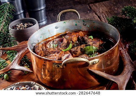 Copper Pot of Venison Goulash Stew Seasoned with Fresh Herbs Surrounded by Evergreen Sprigs and Deer Antlers - stock photo