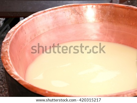 copper pot with the milk and the whey for the production of cheese