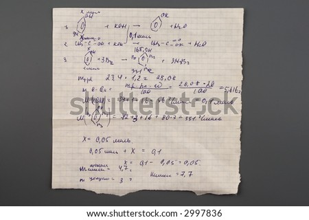 Copy-book sheet of paper with formulas isolated over gray - stock photo