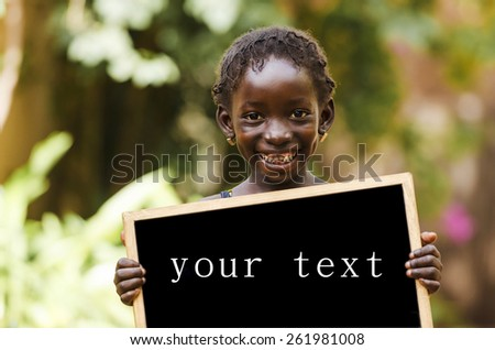 Copy Space - African Girl Holding Chalkboard. Education Symbol with African girl in Bamako, Mali. - stock photo