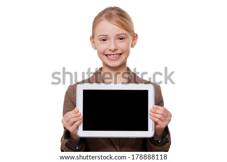 Copy space at her tablet. Cheerful little girl in formalwear showing her digital tablet and smiling while standing isolated on white - stock photo