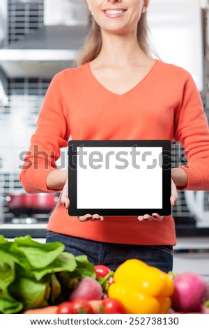 Copy space at her tablet. Cheerful young woman holding digital tablet standing in her kitchen at home - stock photo