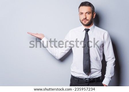 Copy space at his hand. Confident mature man in shirt and tie holding copy space and looking at camera while standing against grey background - stock photo
