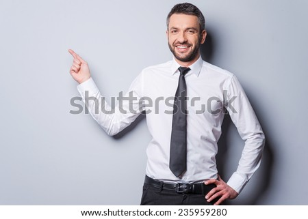Copy space at his hand. Happy mature man in shirt and tie pointing copy space and smiling while standing against grey background - stock photo