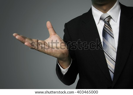 copy space for add text on hand, Asian businessman reach hand for hold present financial analysis, businessman with virtual screens ,banker present financial growing up on gray wall background.
