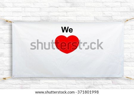 Copy space for text and red heart shape on disastrously white vinyl banner on brick background .Clipping path horizontal