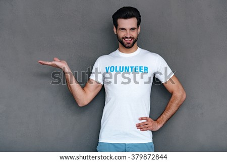Copy space in his hand. Confident young man in volunteer t-shirt holding copy space in his hand and looking at camera with smile while standing against grey background